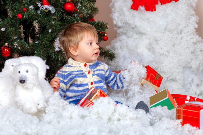 O rapaz pequeno próximo decorou a árvore de Natal imagens de stock royalty free