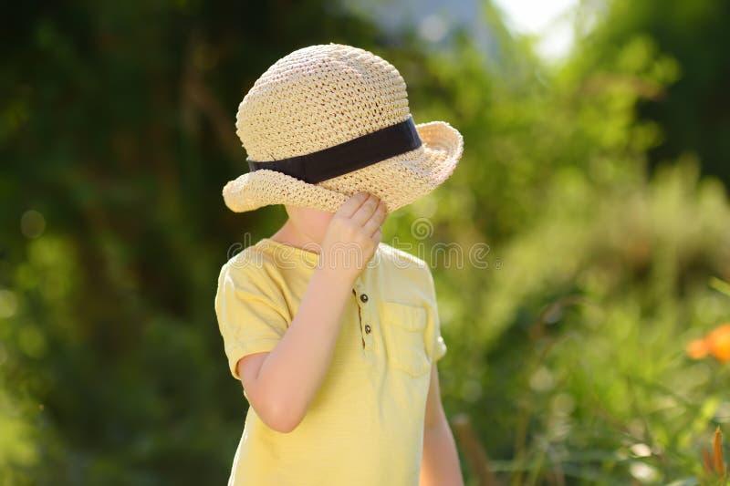 O rapaz pequeno que engana ao redor, cobre sua cara com um chapéu de palha imagens de stock