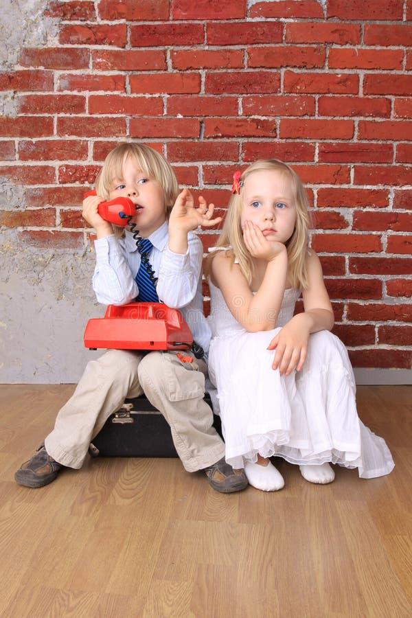 O rapaz pequeno que fala no telefone, menina é furado fotos de stock
