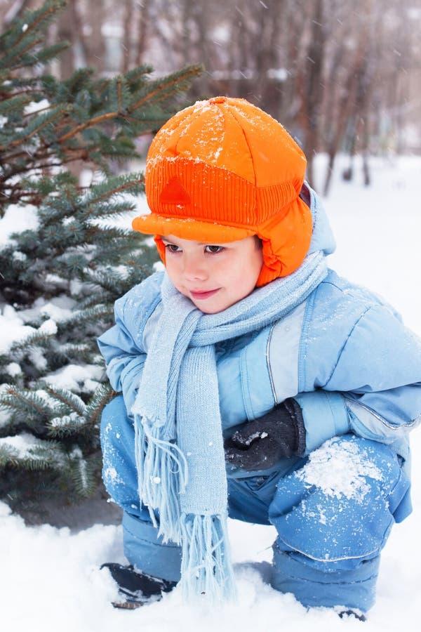O rapaz pequeno que joga snowballs, boneco de neve sculpts imagem de stock