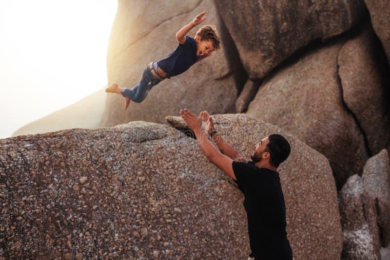 O rapaz pequeno que pula em seu ` s do pai arma-se na praia imagem de stock royalty free