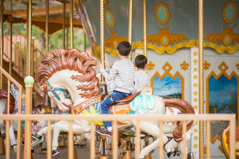 O rapaz pequeno que senta-se dentro casa-se vai circularmente no parque de diversões fotos de stock royalty free