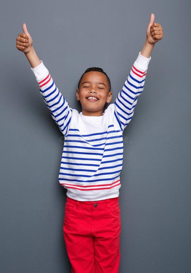 O rapaz pequeno que sorri com polegares levanta o sinal foto de stock royalty free