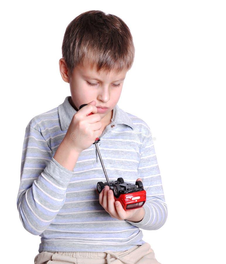 O rapaz pequeno repara o automóvel fotos de stock