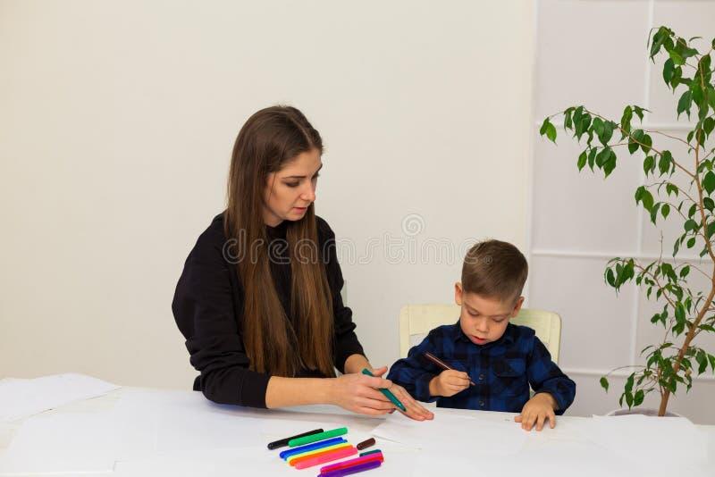 O rapaz pequeno seleciona marcadores da mãe da lição fotos de stock