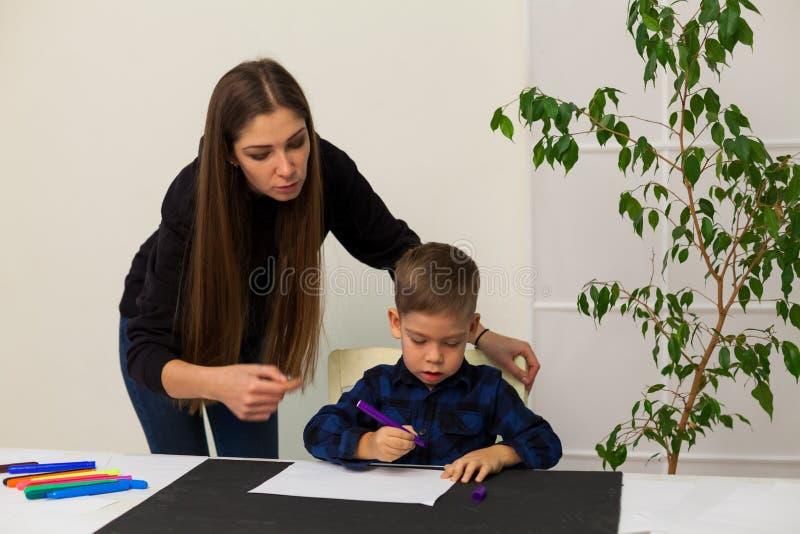 O rapaz pequeno seleciona marcadores da mãe da lição imagem de stock