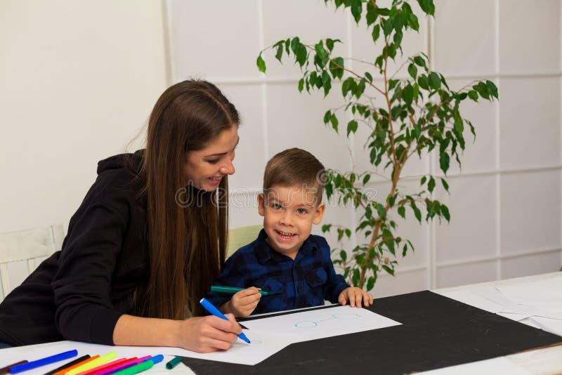 O rapaz pequeno seleciona marcadores da mãe da lição fotos de stock royalty free