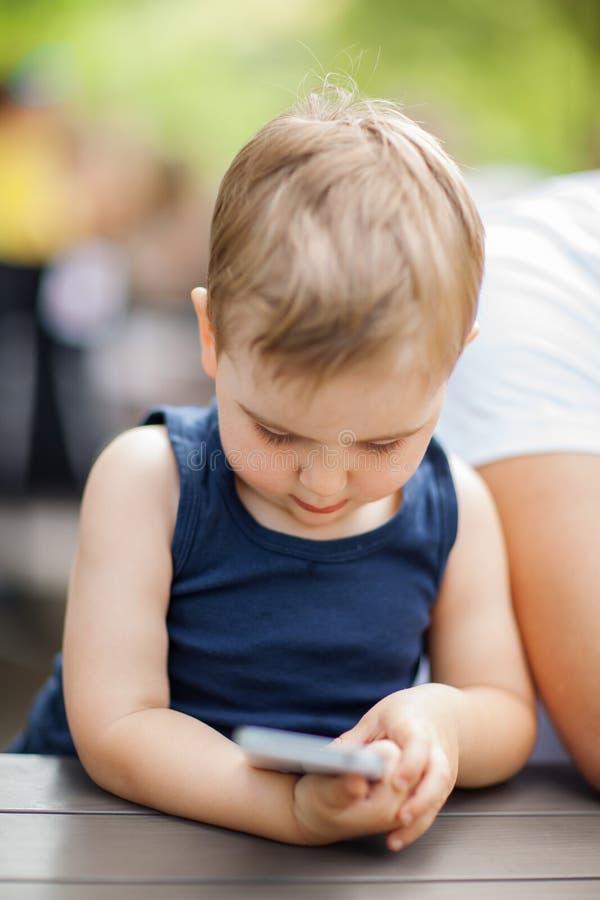 O rapaz pequeno senta-se ao lado do paizinho e é concentrado altamente com um telefone celular em suas mãos imagens de stock royalty free