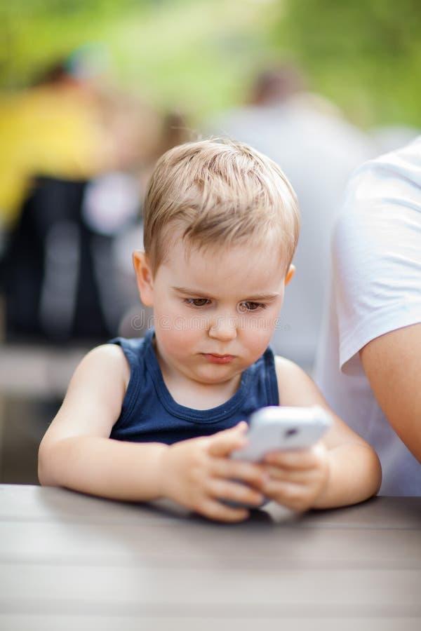 O rapaz pequeno senta-se ao lado do paizinho e é concentrado altamente com um telefone celular em suas mãos fotografia de stock
