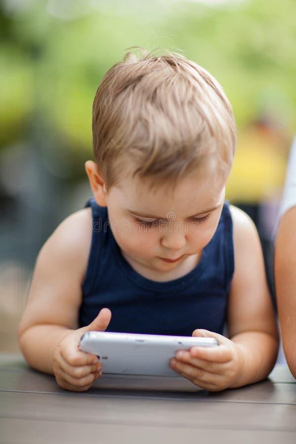 O rapaz pequeno senta-se ao lado do paizinho e é concentrado altamente com um telefone celular em suas mãos imagem de stock