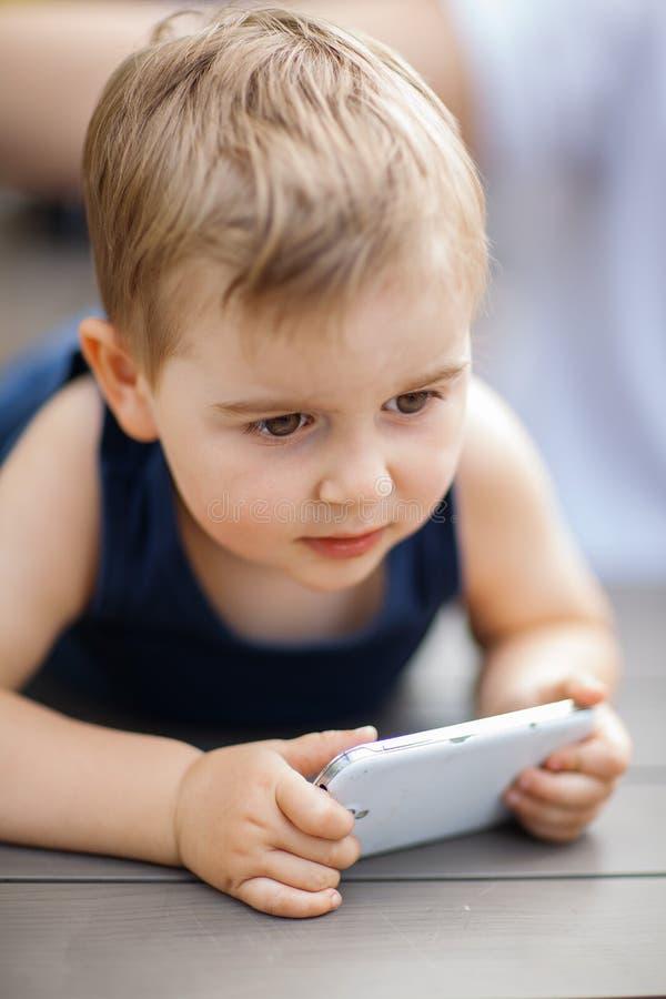 O rapaz pequeno senta-se ao lado do paizinho e é concentrado altamente com um telefone celular em suas mãos fotos de stock