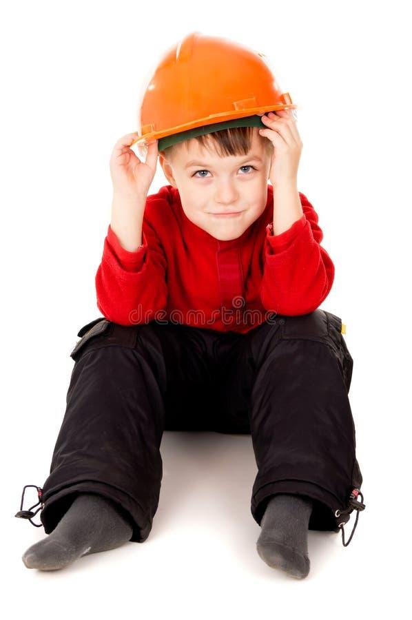 O rapaz pequeno senta-se com um capacete imagem de stock
