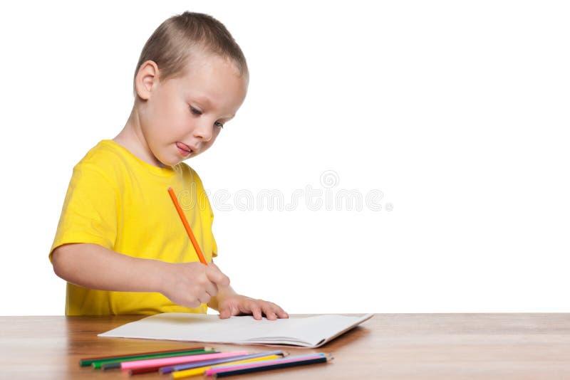 O rapaz pequeno senta-se na mesa e escreve-se foto de stock