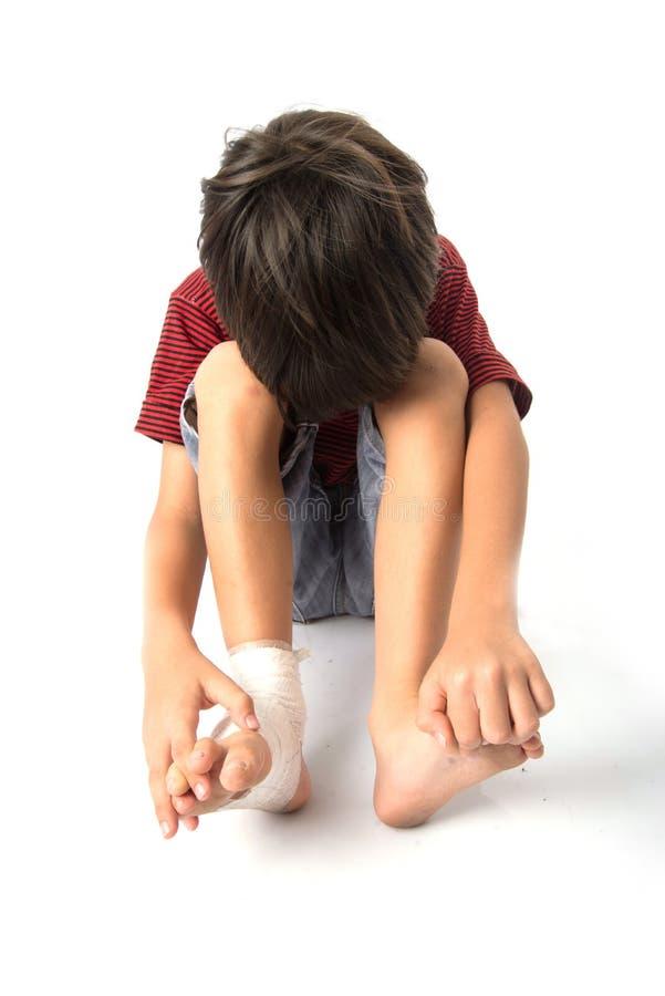 O rapaz pequeno tem um acidente com sua atadura da necessidade do pé para primeiros socorros no baclground branco fotos de stock