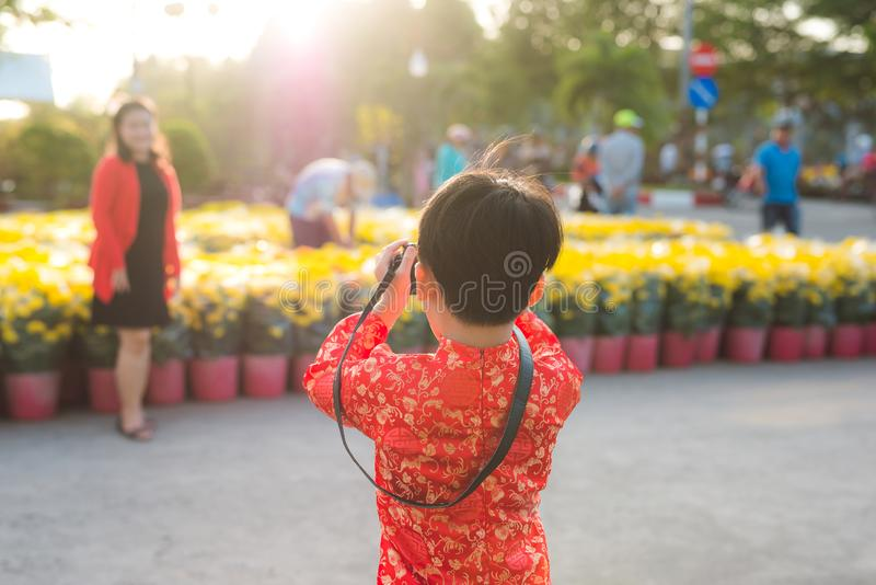 O rapaz pequeno toma uma foto de sua mãe na câmara digital no mercado da flor de Tet fotos de stock