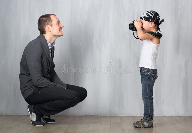 O rapaz pequeno toma uma foto de um homem foto de stock