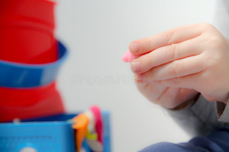 O rapaz pequeno três anos velho senta-se na tabela e os jogos com plasticine e brinquedos, cubos e dados de madeira e plásticos fotos de stock
