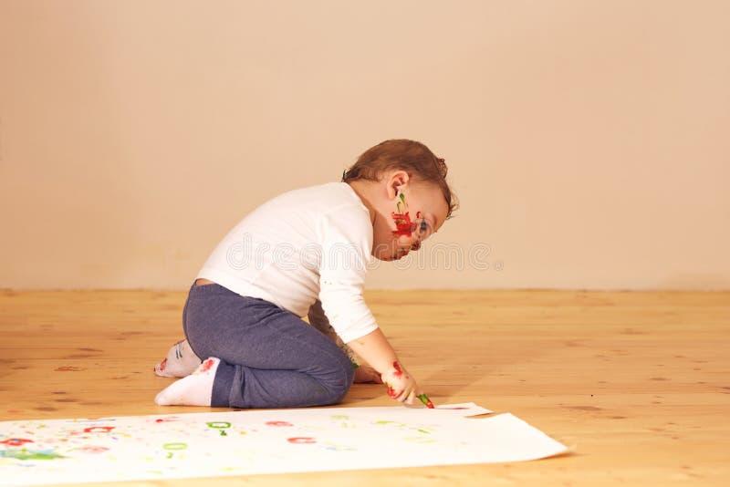 O rapaz pequeno vestido na roupa da casa está sentando-se no assoalho de madeira na sala e está pintando-se com os dedos no papel imagens de stock