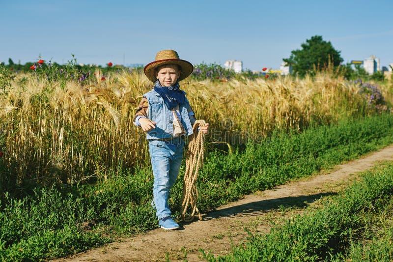 O rapaz pequeno vestiu-se no estilo ocidental no campo fotos de stock royalty free