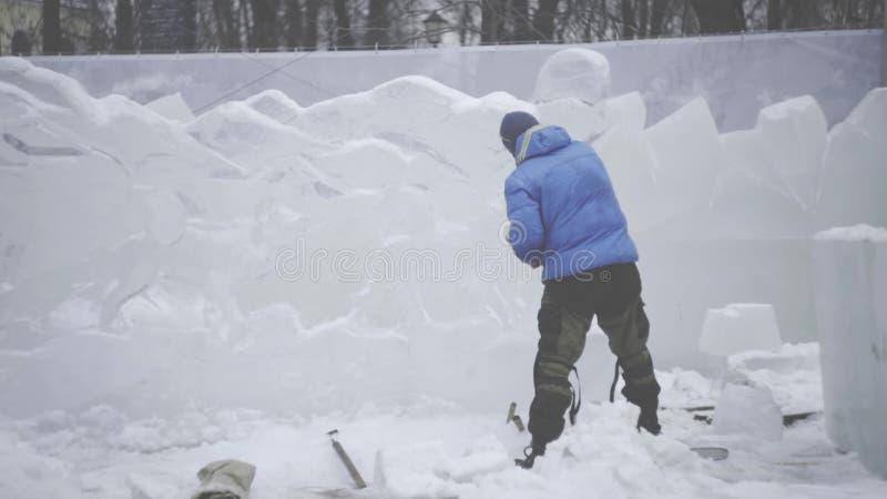 O raspador mestre executa um movimento através do gelo para criar uma escultura de gelo Ferramenta especial de utilização mestra  vídeos de arquivo