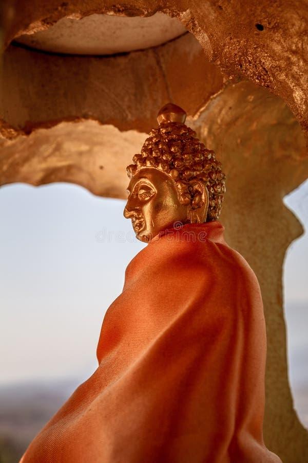 O rebaixo dourado com a estátua elegante da Buda do ouro drapejou na veste budista alaranjada fotos de stock royalty free