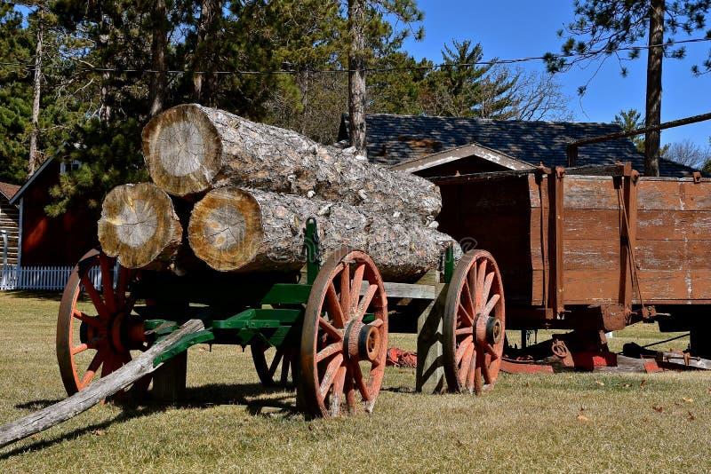 O reboque de madeira velho da roda carregou com os logs enormes imagens de stock royalty free