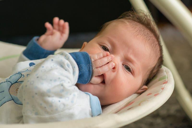 O recém-nascido encontra-se na cadeira elétrica automática do balanço e aprecia-se a fotos de stock