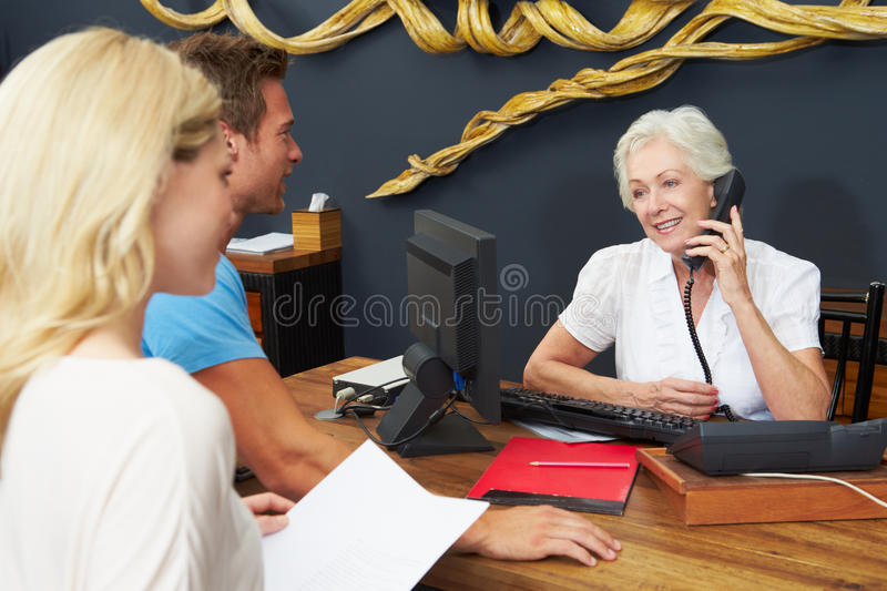 O recepcionista Helping Couple To do hotel verifica dentro imagens de stock