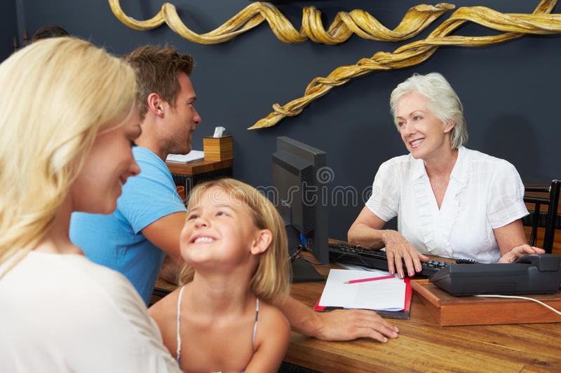 O recepcionista Helping Family To do hotel verifica dentro fotos de stock