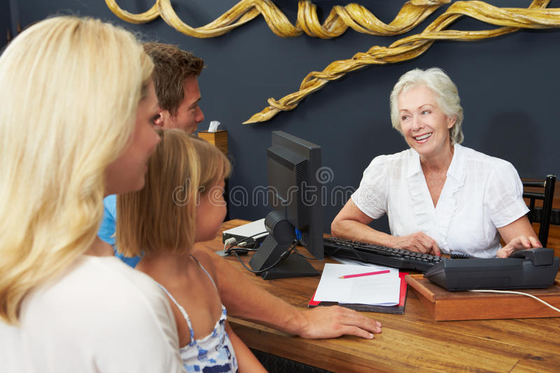 O recepcionista Helping Family To do hotel verifica dentro fotografia de stock royalty free