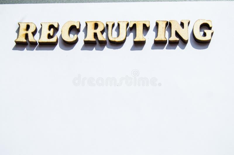 O recrutamento da palavra é escrito em letras de madeira em um fundo branco, o conceito de empregados de aluguer, recrutamento no foto de stock