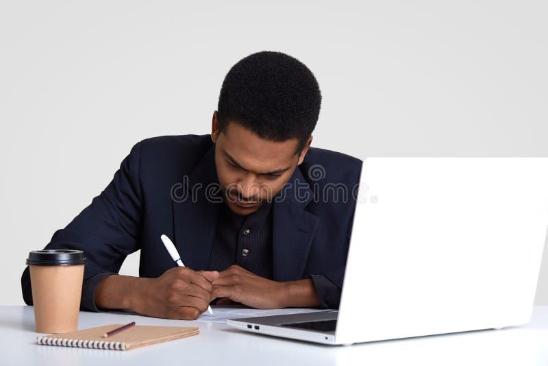 O redator criativo escreve para baixo ideias, senta-se na frente do laptop aberto, cercado com bloco de notas, copo dispoasable d imagem de stock royalty free