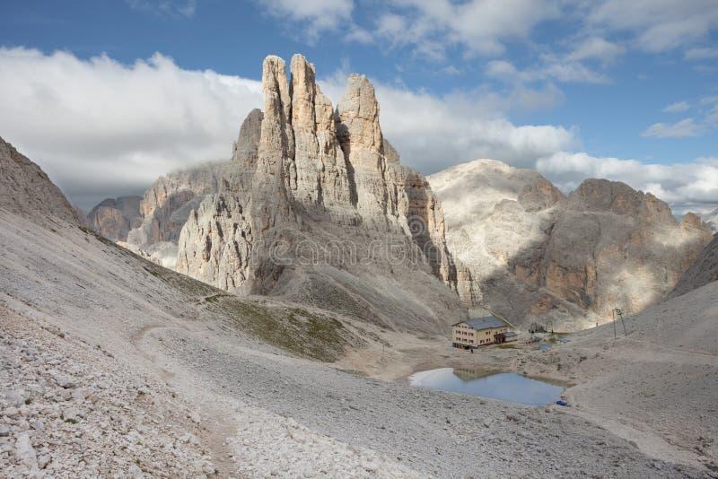 O refúgio de Montain está refletindo sobre um lago pequeno ao lado das torres de Vajolet imagem de stock royalty free