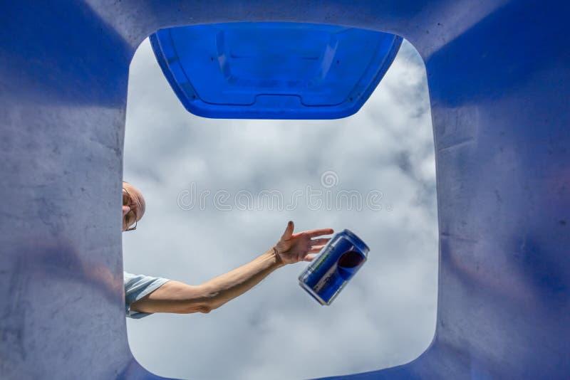 O refresco deixando cair do homem pode no escaninho de reciclagem azul do wheelie imagem de stock royalty free