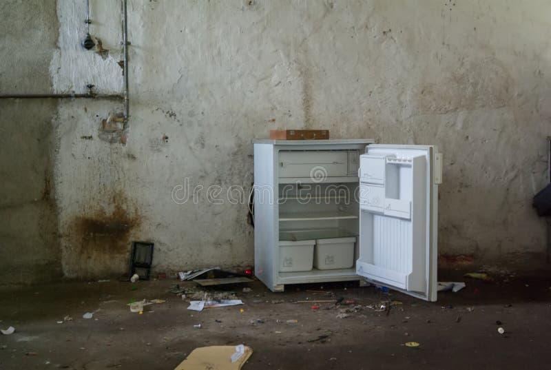 O refrigerador quebrado velho abriu em uma construção abandonada fotos de stock