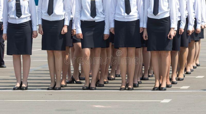 O regimento fêmea em saias pretas e as camisas brancas mantêm um sistema imagem de stock