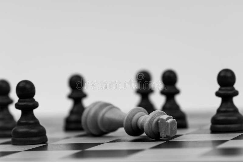 O rei na xadrez caiu a diversos penhores foto de stock