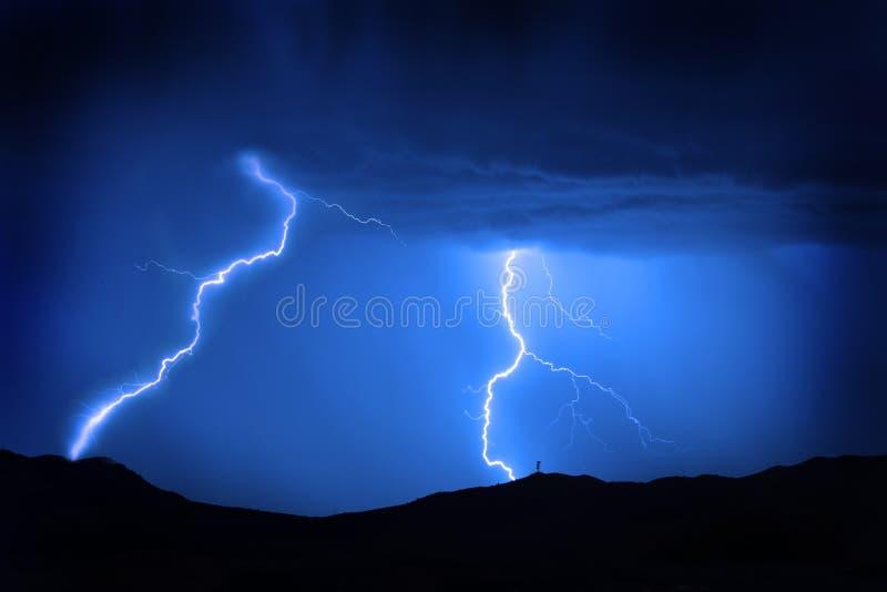 O relâmpago aparafusa na montanha com o céu azul de torre de rádio fotografia de stock