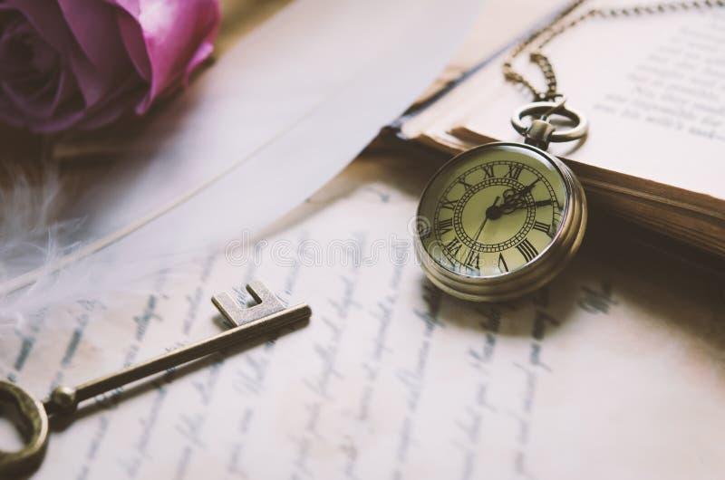 O relógio de bolso antigo e a chave velha do vintage com vintage tonificam fotografia de stock