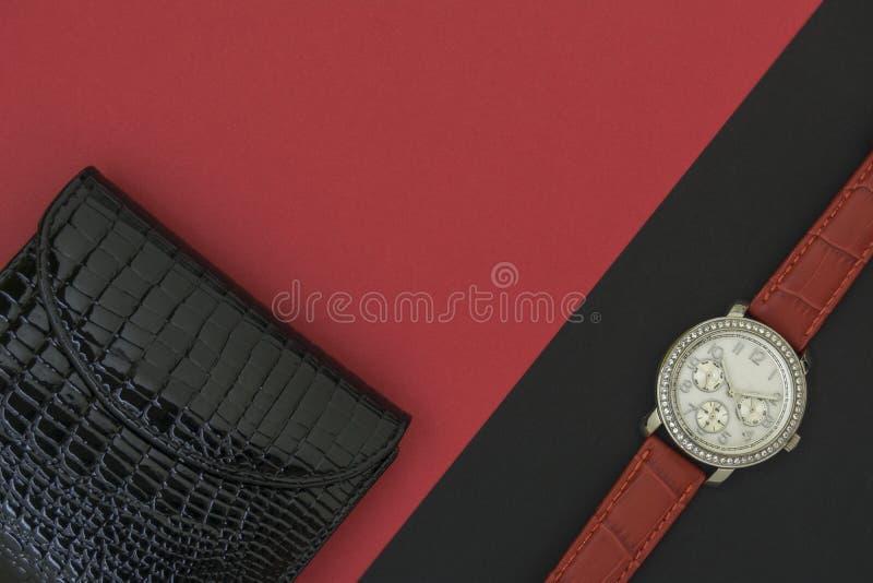 O relógio de pulso das mulheres bonitas no fundo preto A carteira das mulheres negras bonitas em um fundo vermelho imagens de stock