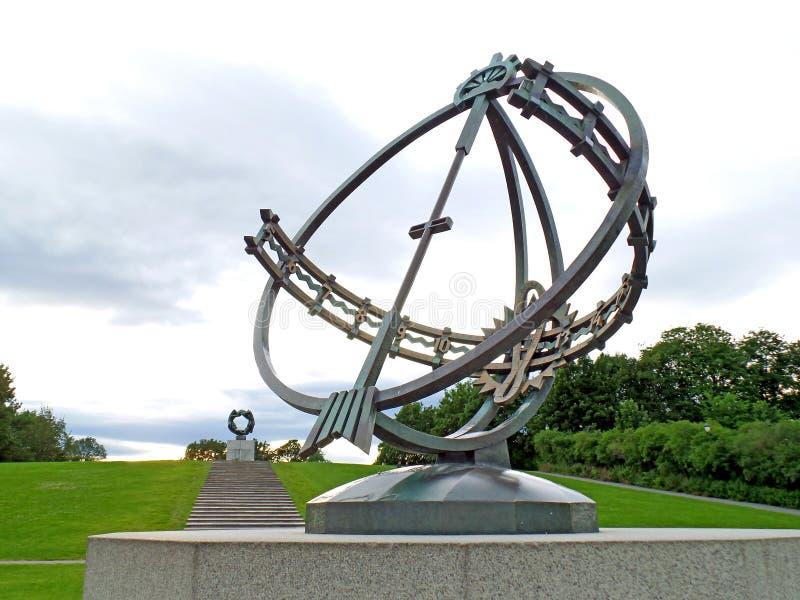 O relógio de sol com a roda da vida no fundo distante, a instalação famosa de Vigeland no parque de Frogner de Oslo, Noruega foto de stock