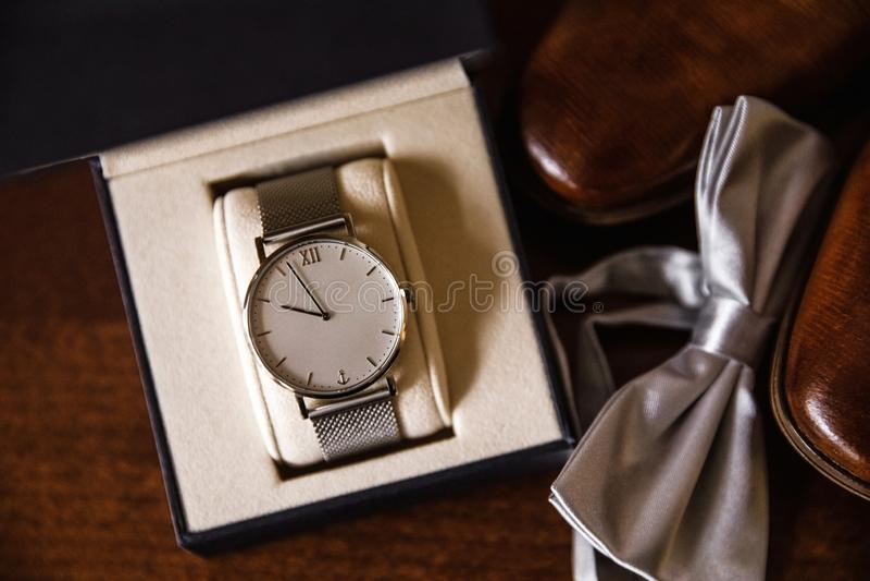 O relógio dos homens em uma tabela com sapatas e uma borboleta Acessórios do casamento no fundo marrom de madeira fotografia de stock royalty free