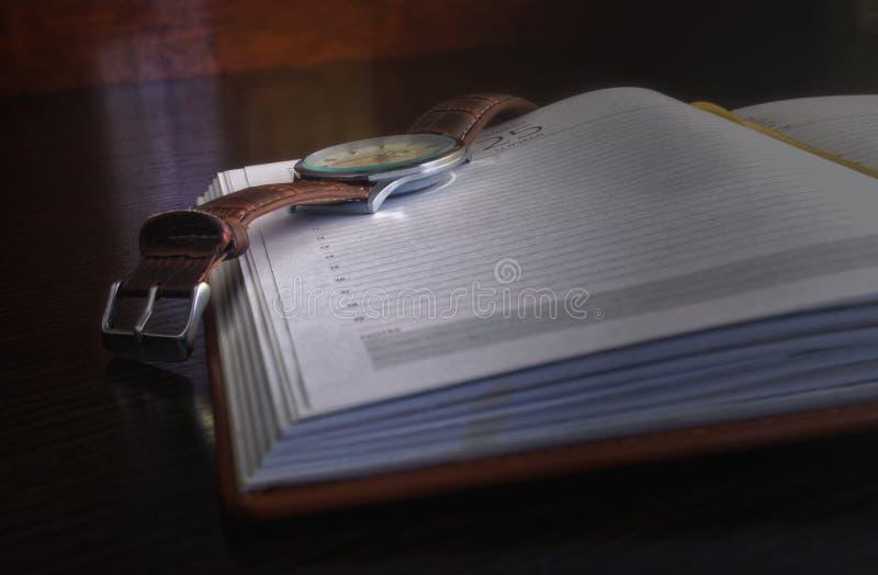 O relógio encontra-se no log diário aberto imagem de stock royalty free