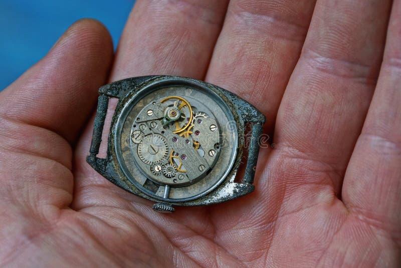 o relógio velho com um mecanismo aberto encontra-se na palma da mão fotos de stock