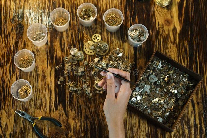 O relojoeiro da mulher trabalha no fundo marrom foto de stock royalty free