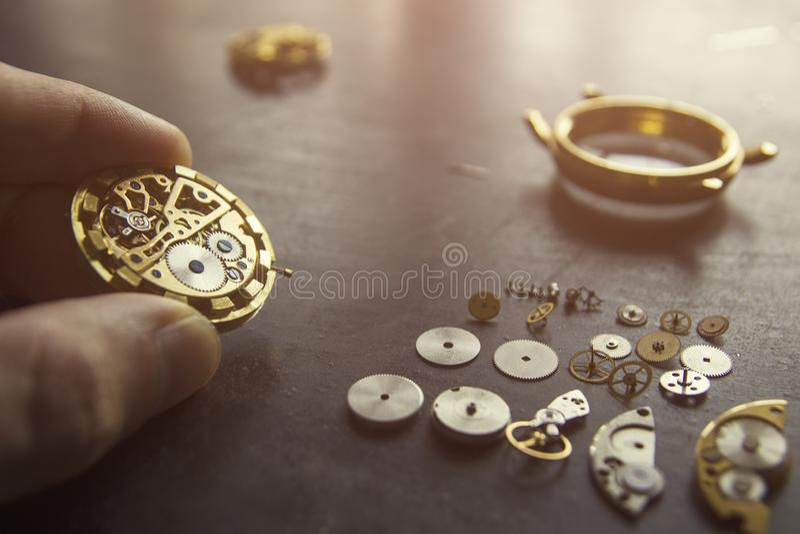 O relojoeiro está reparando os relógios mecânicos em sua oficina fotografia de stock royalty free