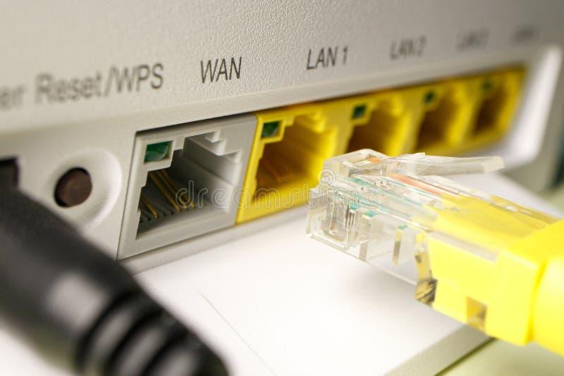 O remendo amarelo do cabo é introduzido no primeiro porto do router da casa imagens de stock royalty free