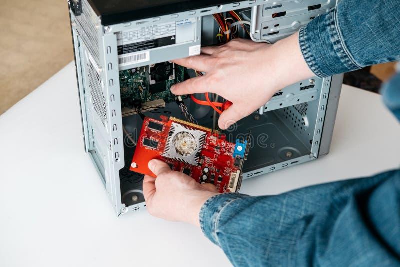 O reparador deve decolar a unidade de processamento gráfica do computador pessoal O coordenador é PC quebrado diagnóstico e fixan imagem de stock
