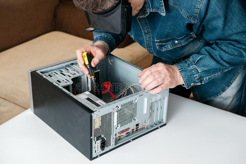O reparador está desmontando o computador pessoal O coordenador é PC quebrado diagnóstico e fixando na oficina foto de stock royalty free