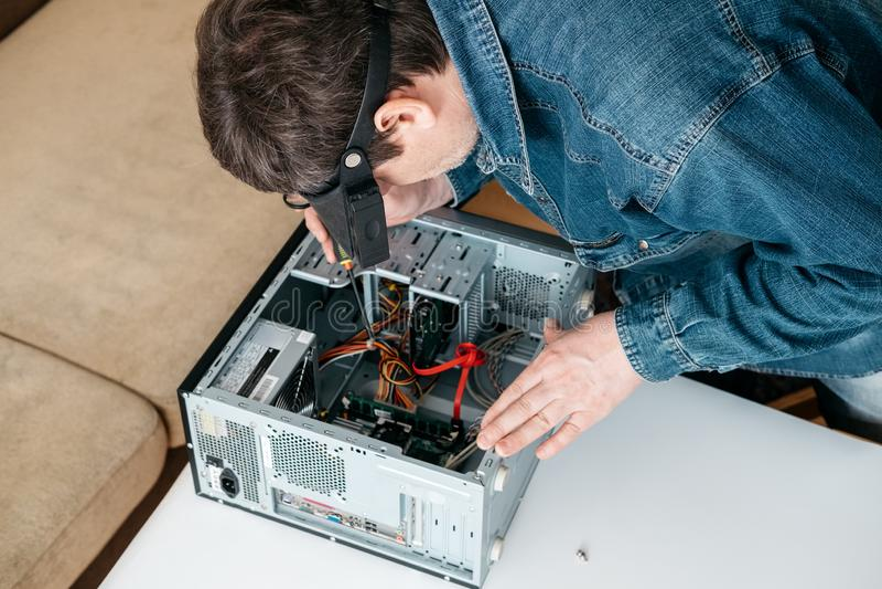 O reparador está desmontando o computador pessoal O coordenador é PC quebrado diagnóstico e fixando na oficina fotos de stock royalty free